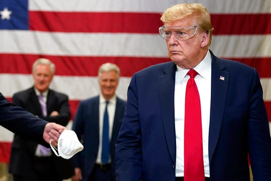 President Donald Trump participates in a tour of a Honeywell International plant that manufactures personal protective equipment, Tuesday, May 5, 2020, in Phoenix. He wore no mask.