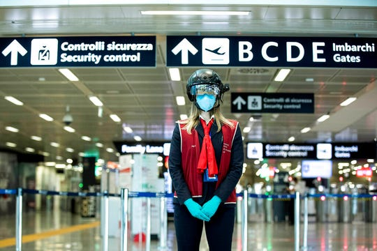 A worker wears a ' smart helmet ' scanner to measure the body temperature of passengers, at the Rome Leonardo da Vinci international airport, Wednesday, May 6, 2020. The number of people who have recovered from coronavirus in Italy is higher than the number of people who are actually positive for the first time since Italy created the first red zones on Feb. 21.