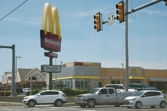 Cars drive by a McDonald's restaurant Thursday, May 7, 2020, in Oklahoma City, where three McDonald's employees suffered gunshot wounds when a customer opened fire because she was angry that the restaurant's dining area was closed because of the coronavirus pandemic, on Wednesday.