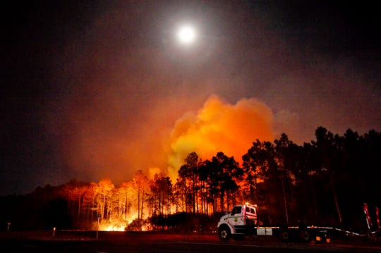 A Florida forestry tractor trailer is parked in Walton County, Fla., near a hot spot from a wildfire, Wednesday.