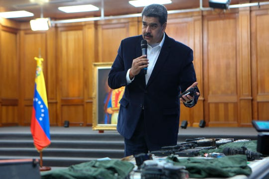 This photo released by the Venezuelan Miraflores presidential press office shows President Nicolas Maduro speaking over military equipment that he says was seized during an incursion into Venezuela, during his televised address from Miraflores in Caracas, Venezuela, Monday, May 4, 2020.