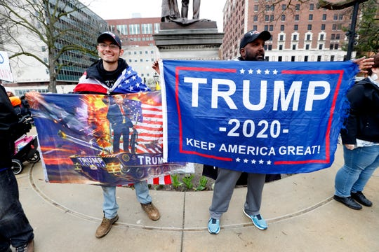 Maskless protesters hold banners supporting President Trump at the State Capitol in Lansing, Mich., Thursday, April 30, 2020.