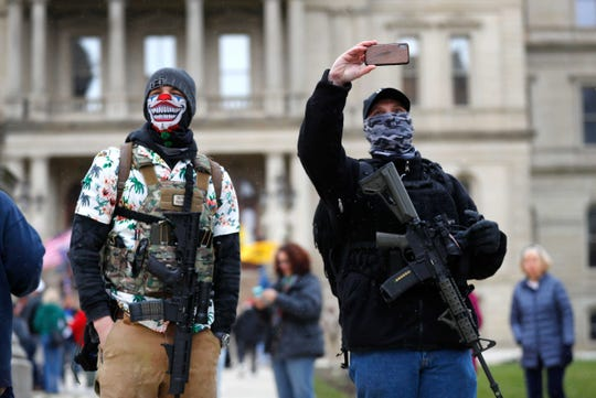 Protesters with rifles watch outside the State Capitol in Lansing, Mich., Wednesday, April 15, 2020. Some Lansing protesters wore masks, but whether for protection from the coronavirus or just to hide their identity isn't certain.