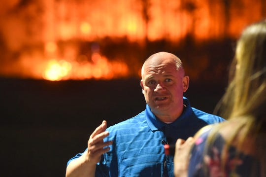 Walton County, Fla., Sheriff Michael Adkinson gives a Facebook live update on a wildfire in the county as a stand of trees burns behind him on Wednesday.