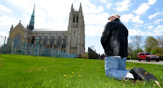Barry Doherty, of Ortonville, kneels as he Prays the Rosary in front of the Cathedral of the Most Blessed Sacrament on Woodward Ave. in Detroit.