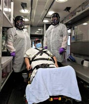 Julie Caponi, Paramedic, and Jodi Brown, Emergency Medical Technician, wear protective gear due to the COVID-19 pandemic in a demonstration, with Port Clinton Mayor Mike Snider posing as a patient.