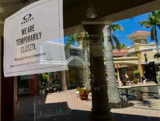 A couple is reflected in the front doors of the closed Oakley store at Miromar Outlets as they ride their bikes on Thursday, May 7, 2020, in Estero. Some of the stores and restaurants are open at the mall. Many of the stores remain closed for now.