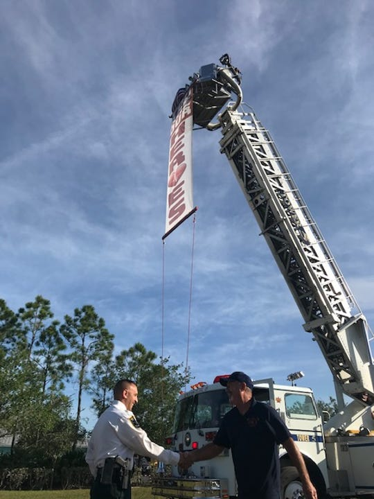 """Nick Libretto, a Cape Coral businessman, shakes hands with Lee County Sheriff Carmine Marceno after he set up a banner Thursday with a heartfelt """"You Are Out Heroes in the vacant field next to LCSO's Six Mile Cypress headquarters"""
