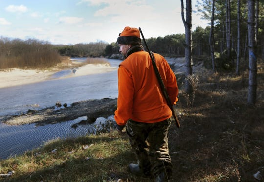 Greg Boley takes in a view of the Eau Claire River before heading back out into the woods during the gun deer hunt season opener on public land in Fall Creek, Wis., on Nov. 19, 2016. Outdoor enthusiasts overwhelmingly rejected Wisconsin wildlife officials' proposals to dramatically reshape the state's gun deer hunting structure to bolster the waning sport, a survey released Wednesday, May 6, 2020, shows.
