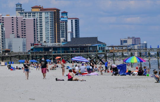 People walk by others sitting in the sand and playing in the Atlantic Ocean in South Myrtle Beach, South Carolina Wednesday, May 6, 2020.