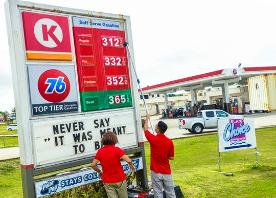 Employees, Feb Tombocn, right, and Virgie Caoile, update a sign to reflect an increase in gas prices at the Dededo 76/Circle K refueling station on Thursday, May 7, 2020. The price of most fuels were  increased by 15 cents.