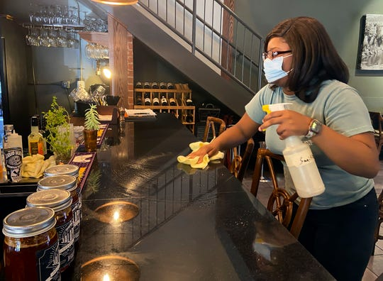 In this March 6, 2020, photo, Zykerial Miller cleans the bar at the Harvest Grill in Meridian, Miss. The restaurant plans to open Friday, May 8, under new COVID-19 guidelines. Some Mississippi restaurants are starting to reopen their dining rooms as the governor eases some coronavirus restrictions, and legislators return to the Capitol to consider aid for businesses hurt by the pandemic. (Bill Graham/The Meridian Star via AP)