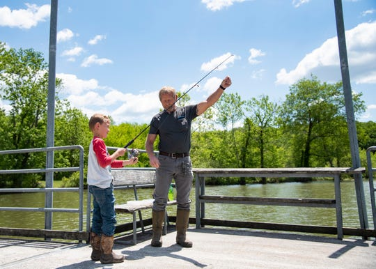 Bobby Lemarr hooks a lure on seven year old Tanner Witick's fishing pole in Cove Lake State Park in Caryville, Tenn., on Thursday, May 7, 2020.