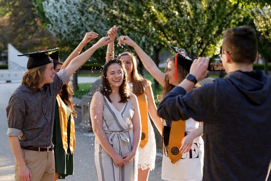 Sydney Sofronici reacts as her friends sprinkle flower petals around her head as they pose for graduation photos by the Engineering Fountain, Wednesday, May 6, 2020 at Purdue University in West Lafayette.