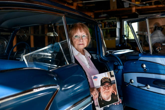 Barbara Kowalk holds a photograph of her late husband Arthur while sitting in his 1958 Chevrolet Bel Air on Wednesday, May 6, 2020, in Lansing. Arthur, a Vietnam veteran and classic car enthusiast, died on April 13. He had been hospitalized with other health issues, but shortly before his death was diagnosed with COVID-19.