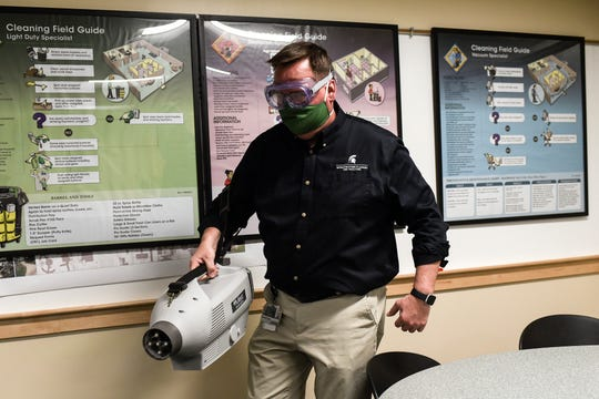 Brandon Baswell demonstrates how a disinfecting misting machine works in a room at the Infrastructure Planning and Facilities building on Friday, May 1, 2020, on the MSU campus in East Lansing. The machine blows a mist of disinfecting solution on to surfaces very quickly and efficiently.