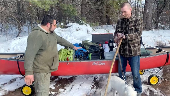 Nate Denofre, left, and Don Jokinen stand in front of one of the canoes they plan to paddle the length of the Mississippi River beginning in May 2020.