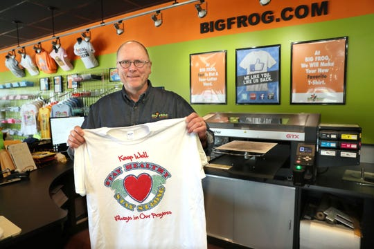Basil Bearer, owner of Big Frog Custom T-Shirts & More in Mequon, shows off a T-shirt similar to the personalized ones Big Frog is printing for seniors living at select Milwaukee-area facilities. They have produced 300 so far.