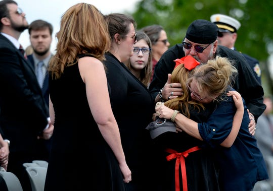 Family members of Spring Hill firefighter Mitchell Earwood including his mother Kathy Brewer, right, and her husband Mark Brewer, top right, who is kissing the head of Earwood's daughter, Lyla Kathleen Earwood, at the funeral on Thursday, May 7, 2020, in Franklin, Tenn. Earwood was off-duty when he died on his family's farm during the storm that swept through Middle Tennessee Sunday night. The service was held outside the church because of social distancing guidelines during the pandemic.