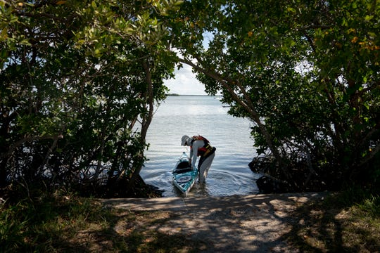 Mark Cecil puts his wife's kayak in the water in Estero Bay on Wednesday, May 6, 2020.