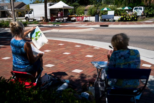 Cheryl Leach, left, and Denni Glick, right, paint scenes of the farmers market off of Old 41 Road in Bonita Springs on Wednesday, May 6, 2020.