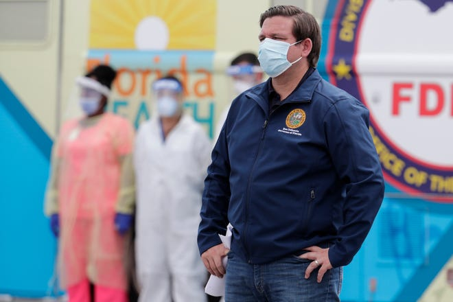 Florida Gov. Ron DeSantis wears a face mask as he listens during a news conference at a COVID-19 testing site at Hard Rock Stadium, during the new coronavirus pandemic, Wednesday, May 6, 2020, in Miami Gardens.