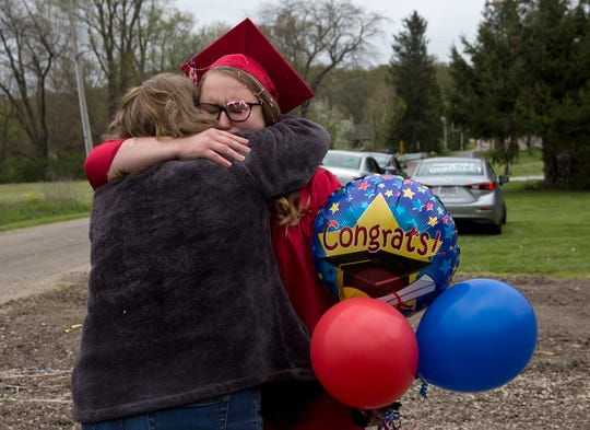 Soon to be Licking Valley graduate Danyelle Stamper hugs her mom after being surprised by a caravan of friends and family who turned out to surprise her for a graduation parade.