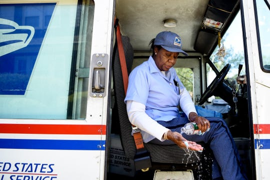 Mail carrier Angela Ross works on her route in Elmwood Park on Thursday May 7, 2020. Ross is worried about her and her family's health and has taken extra precautions to stay safe on the job like washing her hands with soap and bottled water from her truck throughout the day.