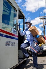 Mail carrier Angela Ross works on her route in Elmwood Park on Thursday May 7, 2020. Ross is worried about her and her family's health and has taken extra precautions to stay safe on the job.