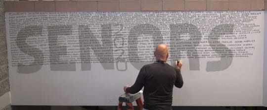 Oñate High School Principal Jim Schapekahm writes the name of each senior on a wall in a video tribute to the class of 2020 posted to YouTube on May 6, 2020.