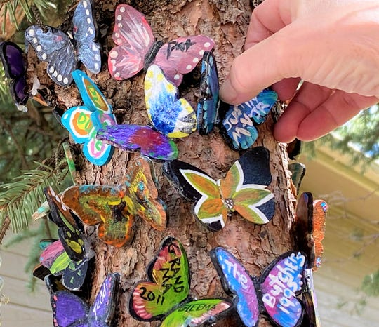 It is a delicate and fragile process placing the butterflies securely on the Peace Tree that takes patience and time. Over 120 butterflies were painted for the tree during a fund raiser for a local food bank.