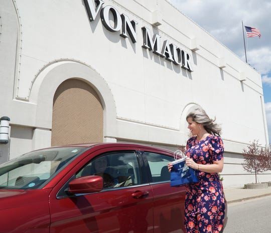 Laurel Park Place's Von Maur employee delivers an item to a waiting car on May 7, 2020. Von Maur and other Laurel Park shops are open at this time to complete orders via curbside delivery.