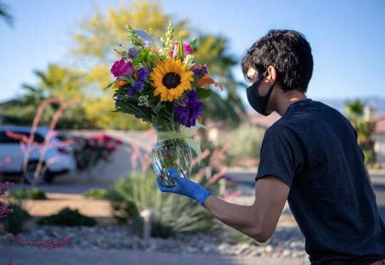 Indio Florist delivery driver Uriel Avila drops off flower bouquets in La Quinta, Calif., on Thursday morning, May 7, 2020.