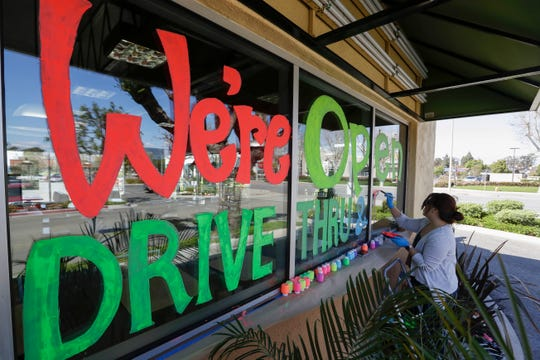 Lucy Kwak paints a sign on the window of a fast food chain's restaurant in Garden Grove on Thursday, March 26, indicating that the drive-thru window is still open -- as well as a takeout option -- during the coronavirus outbreak.