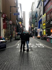 "Kayla Perez and her father pose in Seoul, South Korea the day before heading back to the United States, due to the COVID-19 pandemic. ""It looks a lot more empty than it would normally be,"" Perez said."