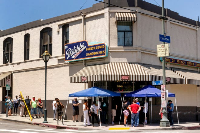 People stand in line Saturday, May 2, while following social distancing guidelines as they wait for French dip sandwiches outside Philippe the Original restaurant in downtown Los Angeles.