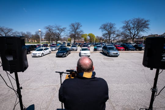 Pastor Phil Whetstone, from Colonial Woods Missionary Church, stands on a small stage, spaced a distance in front of a row of cars, as he leads a group in prayer during a drive-in service on National Day of Prayer Thursday, May 7, 2020, at McMorran in Port Huron. This year, instead of a prayer service and breakfast at the MOC, a drive-in service was held, which allowed people to attend while still practicing social distancing.