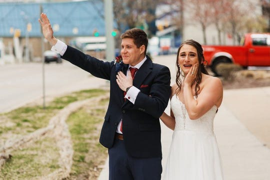 Devin Haberling and Maddy Moldenhauer get emotional as friends and family who were unable to attend their wedding due to the coronavirus pandemic drive past them as a parade of well-wishers afterward at Immanuel Lutheran Church in Grand Rapids on April 25, 2020.