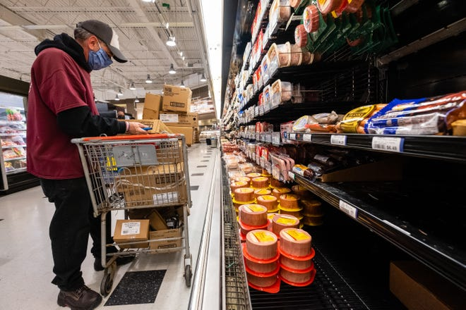 Neiman's employee Brian Zobl stocks lunch meats Thursday, May 7, 2020, in the St. Clair store. Grocery store workers across the country have been working through the coronavirus pandemic while adjusting their routines to meet new cleanliness, sanitation and social distancing guidelines.