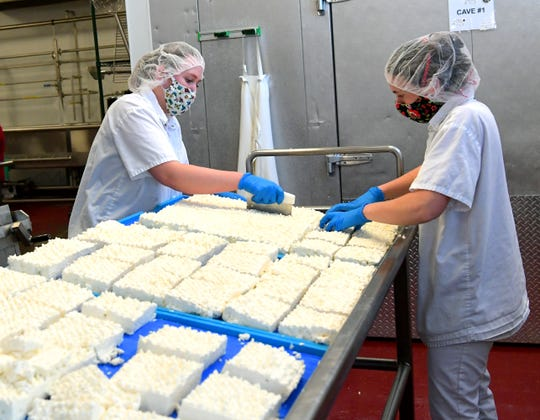 Caputo Brothers Creamery employees Rebeccah Baumgardner, left, and Elizabeth Cornwell prepare cheese for packaging at the Spring Grove business Thursday, May 7, 2020. The company partnered with Tršegs Beer to make a beer cheese which is sold at Giant grocery stores. Bill Kalina photo