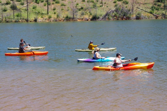 Friends and coworkers of Maria Gomez head out Wednesday for a paddle on Whiskeytown Lake, where the number of visitors in March was 13% above average.