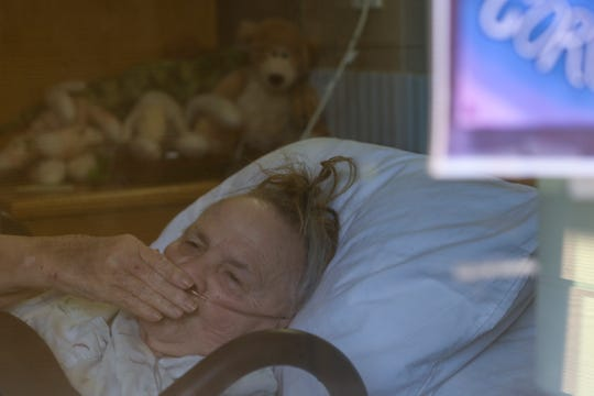 Mary Davis, 81, blows her daughter a kiss through the window as she recovers from COVID-19 in isolation at the Oaks at Sherwood Park in Keizer on May 6, 2020.