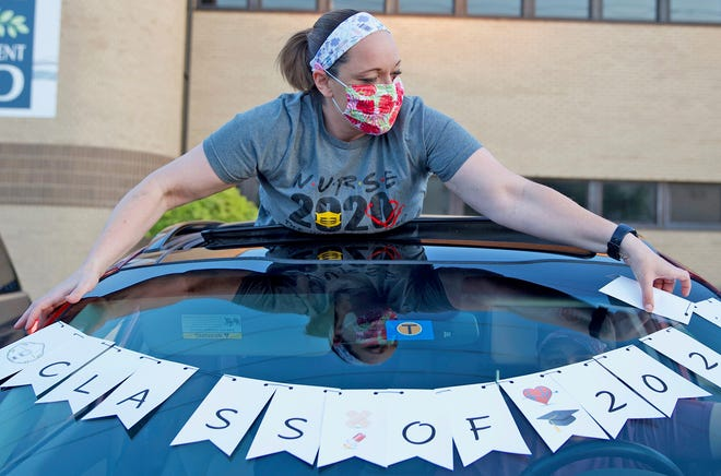 Jodi Belote puts out a sign on her vehicle during a ceremony at Shannon Medical Center to honor nursing students from Howard College on Wednesday, May 6, 2020.
