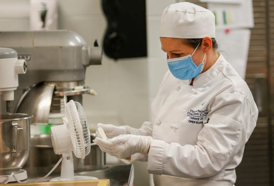 Ondi Burns, a culinary student at OTC, cools off a piece of sugar that she will mold into a goldfish for one of her final projects before graduating. She was glad to be able to return to in-person classes at OTC to finish her degree.