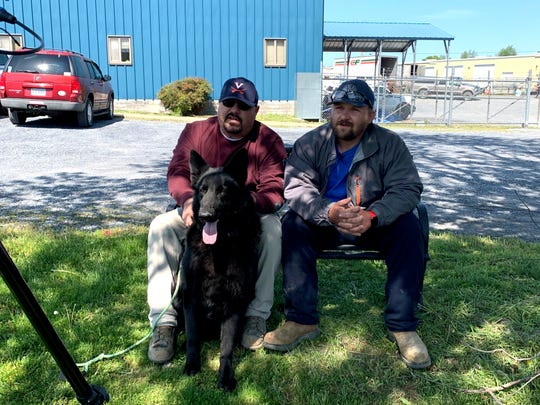 Jay Johnson and Cavaja Holt with Jett Thursday morning, May 7. The two men helped save Jett's life when the dog was choking on a ball Wednesday. Johnson coached, and Holt pulled the ball out of Jett's mouth and gave him mouth-to-mouth resuscitation.