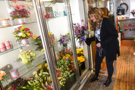 Owner Tracy Omann Smith removes a freshly-prepared arrangement from a case at Daisy A Day Floral & Gift Thursday, May 7, 2020, in St. Joseph.