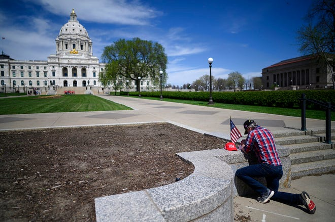A person prays outside the state Capitol in St. Paul on Saturday, May 2, 2020. The 2020 regular legislative session ends May 18.