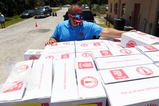 Brian Townsend, facilities manager at Treasure Coast Community Health clinic in Fellsmere, unloads boxes of emergency food rations on Thursday, May 7, 2020, during a food giveaway at the clinic. The boxes of food were provided by the Treasure Coast Food Bank and distributed at locations on Thursday.