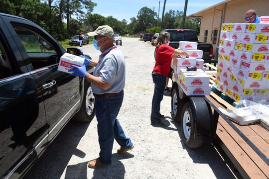 Dennis Bartholomew (left) hands an emergency box of food through the window of a car on Thursday, May 7, 2020, during a food giveaway at Treasure Coast Community Health clinic in Fellsmere. The clinic, in coordination with Treasure Coast Food Bank, distributed about 600 boxes of food at two locations on Thursday. Each box contained staple items such as peanut butter, pasta, canned fruit and vegetables and other non-perishable items that can feed a family of four for about one week.