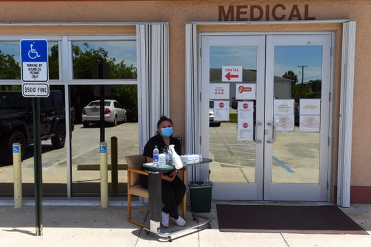 Adriana Contreras, a medical assistant at Treasure Coast Community Health in Fellsmere, sits outside the entrance of the clinic on Thursday, May 7, 2020, to screen patients for symptoms of COVID-19 before they enter the building.